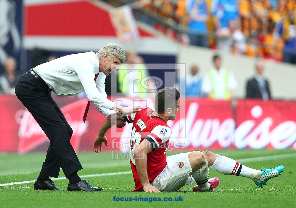 Arsene Wenger ( L ), Manager of Arsenal helps Olivier Giroud to his feet during the The FA Cup Final match at Wembley Stadium, London<br /> Picture by Paul Terry/Focus Images Ltd +44 7545 642257<br /> 17/05/2014