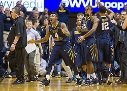 West Virginia Mountaineers guard Daxter Miles Jr. (4) celebrates with teammates during a timeout against the Oklahoma State Cowboys during the first half at the WVU Coliseum.