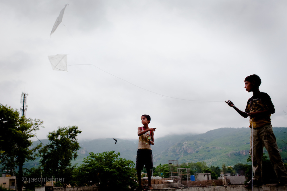 Islamabad: Two young boys fly home made kites at the Christian Colony in Islamabad...Pakistan's Christian communities account for an estimated one percent of the country's 180 million population...I the middle of Islamabad's wealthiest neighbourhood is a 'colony' that's home to some 4000 Christians. Narrow alleys separate multi-storey, squalid houses with open sewers running meandering the alleys to the river that runs through the heart of the colony...Some are recent arrivals from Faisalabad and Gojra, where recent sectarian killings forced many to relocate to the relative safety of the capitol territory. Many are second and third generation residents squatting on land that sees no development assistance from the Capital Development Authority. Power outages are frequent, many residents sleep on the roofs during the long summer months, there are no air-conditioners in the colony...Many of the residents are unemployed; those fortunate to have any income usually work as servants, gardeners, drivers, security guards or cleaners. ..Discrimination against the Christian minorities is rampant in Pakistani society. Many suspect the government of deliberately keeping them at the bottom of the economic ladder to appease the radical religious parties...©JTanner/August2011