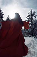 Artistic dynamic photo of a beautiful asian woman in red undone kimono running on the snow through a winter forest into the sunlight