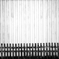 A wooden wall of a house and a wooden fence form a homogeneous whole.
