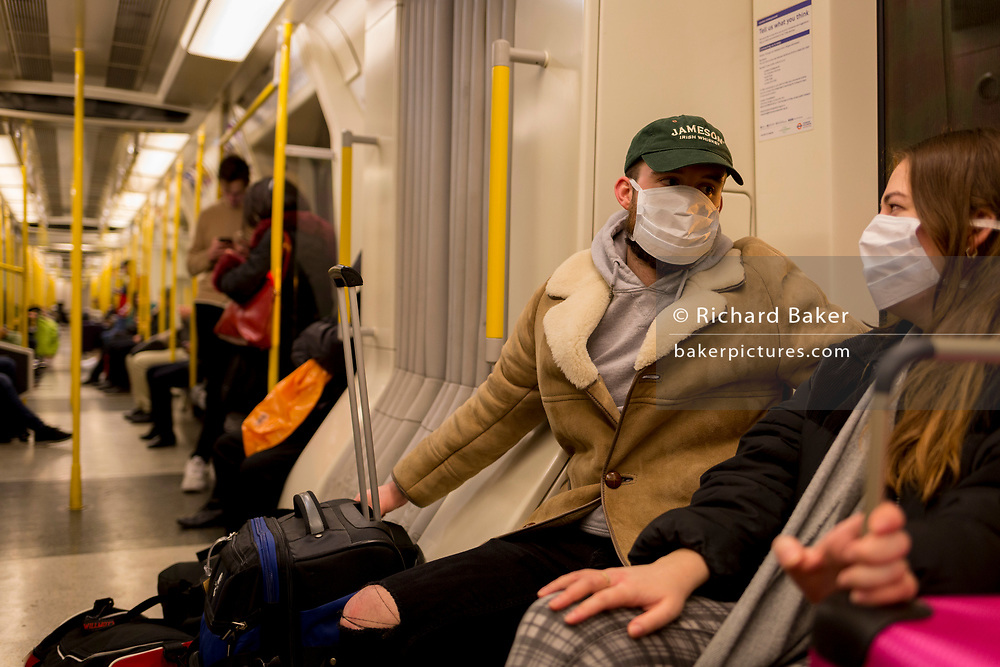As the Coronavirus pandemic spreads across the UK, businesses and entertainment venues not already closed with the threat of job losses, struggle to stay open with growing rumours of a lockdown and travel restrictions around the capital. Londoners start to work from home and a couple of travellers wear face masks during their journey across the capital on the London Underground, on 19th March 2020, in London, England.
