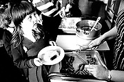 A young schoolgirl waits with a plate to be served her dinner in the school dinner queue Rougemont Prep school Newport Wales c.1990.
