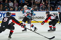 KELOWNA, CANADA - JANUARY 4:  Lassi Thomson #2 of the Kelowna Rockets passes the puck between Mitchell Kohner #25 and Tyson Upper #9 of the Prince George Cougars on January 4, 2019 at Prospera Place in Kelowna, British Columbia, Canada.  (Photo by Marissa Baecker/Shoot the Breeze)