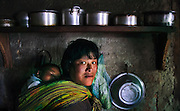 A woman and her baby in her kitchen in Bumthang Bhutan.