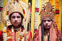 Two children dress up as elaborate goddesses in ornamental garb at kumbh mela