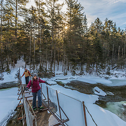 A couple crosses a suspension bridge over the Hudson River near its source in New York's Adirondack Mountains. Upper Works Trail, East River Trail. Tahawus Tract, Newcomb, New York.