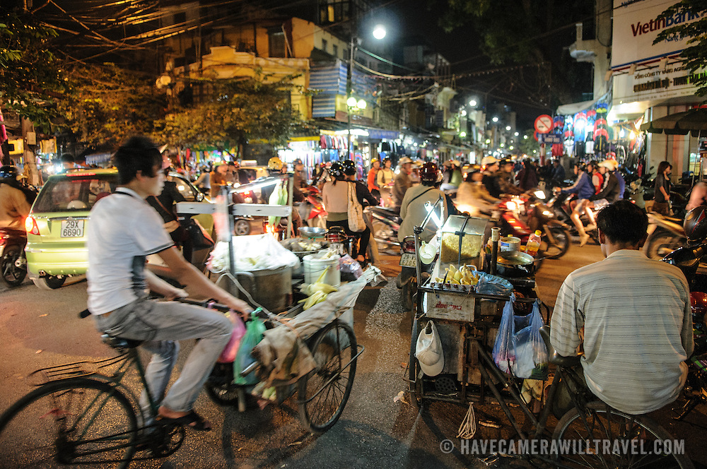 Busy traffic on bicycles and scooters at night in Hanoi's Old Quarter.