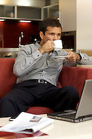 Young man drinking tea, sitting in sofa