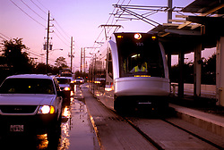 Houston Metro Light Rail alongside early-morning traffic in Houston, Texas.