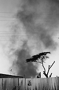 NAIROBI, KENYA - DECEMBER 31, 2007: Residents from Kibera slum stand on rooftops of corrugated metal to get a better view of protesters as they loot and destroy Kikuyu shops and houses. A surge in violence left scores of people dead in Nairobi as defeated presidential candidate Odinga prepared to declare himself head of state, after rejecting the victory of incumbent president Mwai Kibaki.