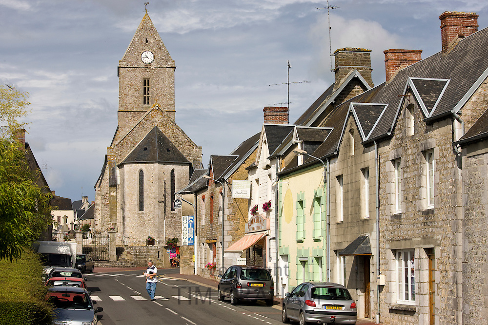 Church and street scene in French town of Trelly in Normandy, France