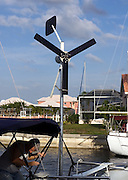 wind generator on stern of sailboat; man working; power production; vertical