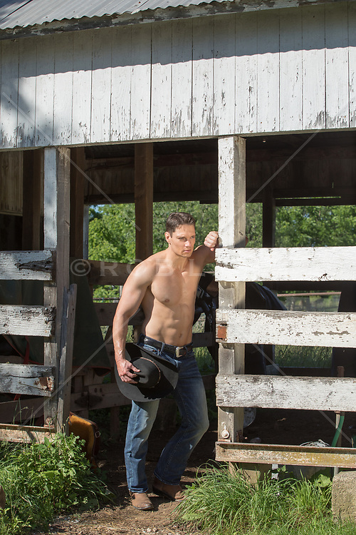 shirtless cowboy by a rustic barn