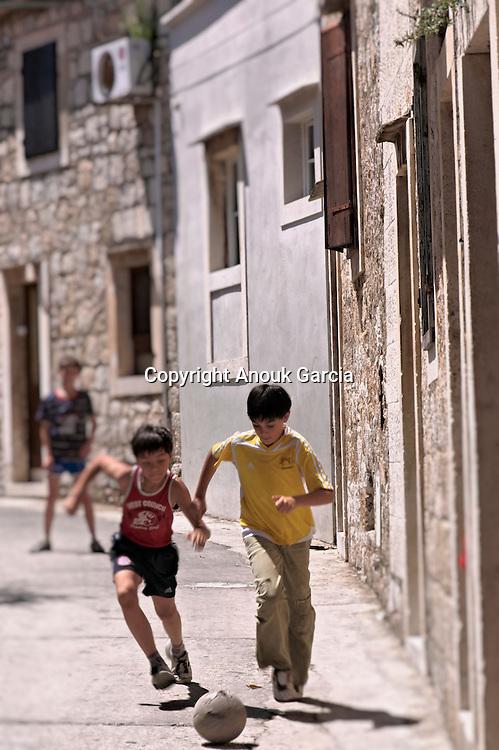 Village of Komiza, young children playing football. | Village de Komiza, jeunes enfants jouant au foot