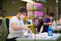 DEU, Deutschland, Germany, Eberswalde, 11.06.2020: Bei der Firma Thorka arbeiten Näherinnen in der Schulranzenproduktion und fertigen zudem Feder- und Sporttaschen. In der Corona-Krise produziert der Schulranzenhersteller (McNeill) auch Mund-Nase-Schutzmasken. Hier eine Frau mit Bügeleisen beim bügeln der Masken. Im Unternehmen gibt es Pläne, in die Herstellung von medizinischen FFP-Masken einzusteigen.