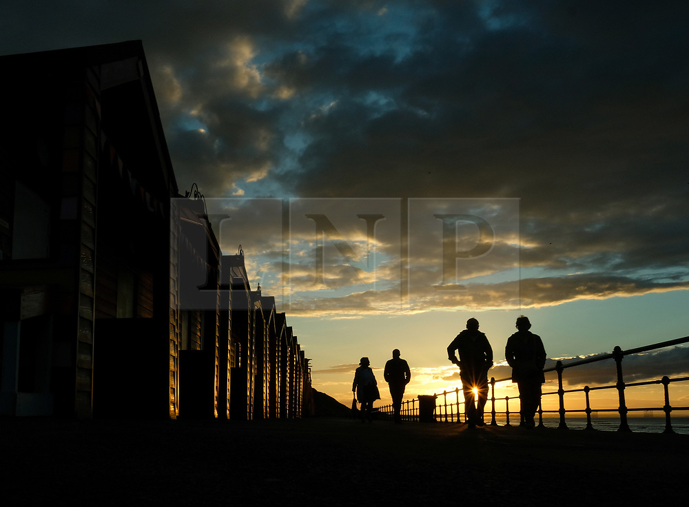 © Licensed to London News Pictures. <br /> 01/08/2017. <br /> Saltburn by the Sea, UK.  <br /> <br /> Couples walk along the seafront promenade as the light from the setting sun is reflected on beach huts in Saltburn by the Sea.<br />   <br /> Photo credit: Ian Forsyth/LNP