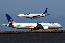Boeing 737-824 (N18223) operated by United Airlines landing past Boeing 787-9 Dreamliner (N27957) operated by United Airlines at San Francisco International Airport (KSFO), San Francisco, California, United States of America