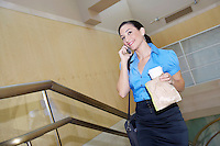 Business woman holding lunch, using mobile phone