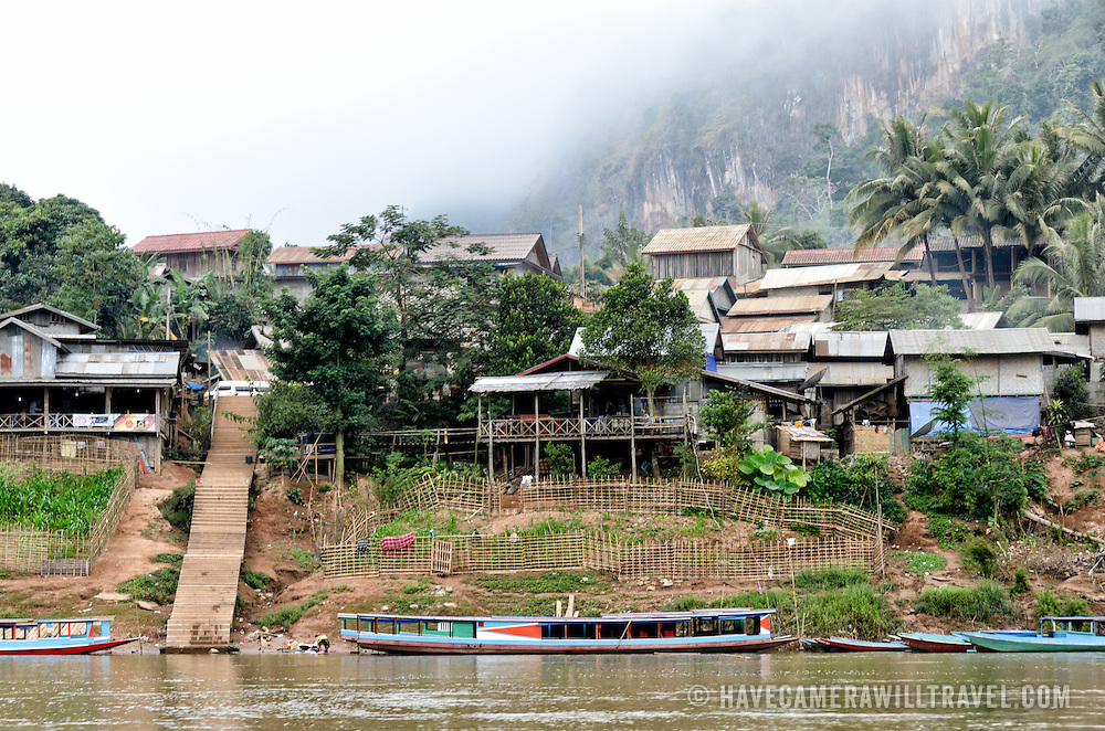 The town of Nong Khiaw nestled on the waterfront of the Nam Ou (River Ou) while morning mists obscure most of the steep, rocky karsts in the background.