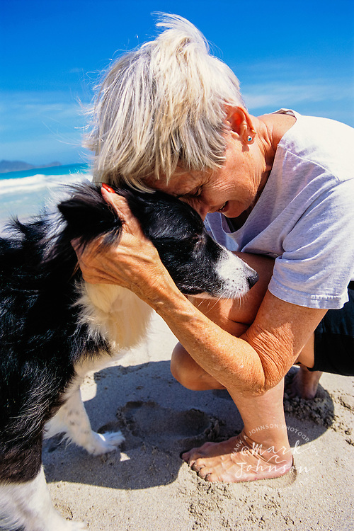 Elderly Women Cuddling Dog on Beach