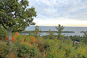 Oranges and reds begin to glow against a backdrop of conifers, with Lake Superior in the background.
