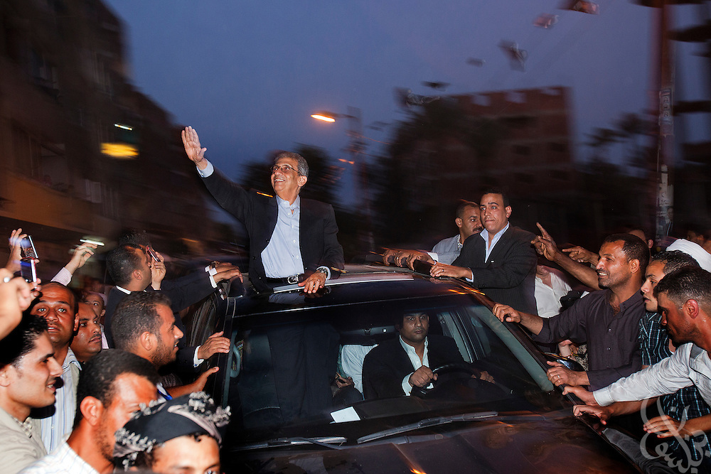 Egyptian presidential candidate Amr Moussa waves to supporters from atop his vehicle as he arrives at a May 16, 2012 campaign stop in the village of Khanka on the outskirts of Cairo, Egypt. Moussa is currently the front-runner in the upcoming Egyptian presidential elections that will take place across the country May 23-24, 2012. (Photo by Scott Nelson)