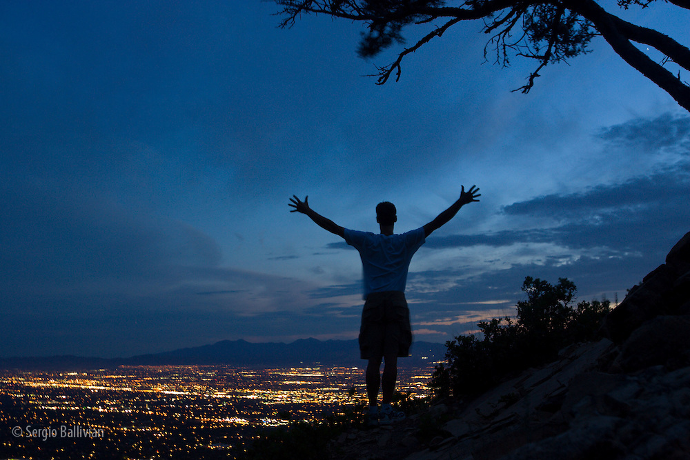 A man is silhouetted against a blue dusk above the bright lights of Salt Lake City in summer.