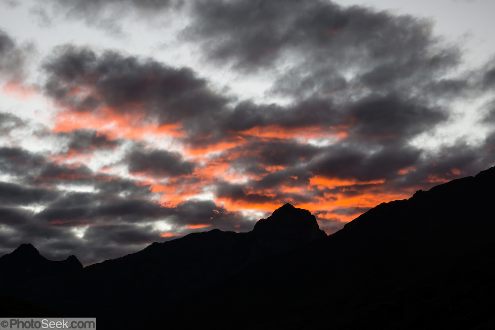 Orange clouds at sunrise on Day 3 of 9 days trekking around the Cordillera Huayhuash in the Andes Mountains, near Huaraz, Peru, South America.
