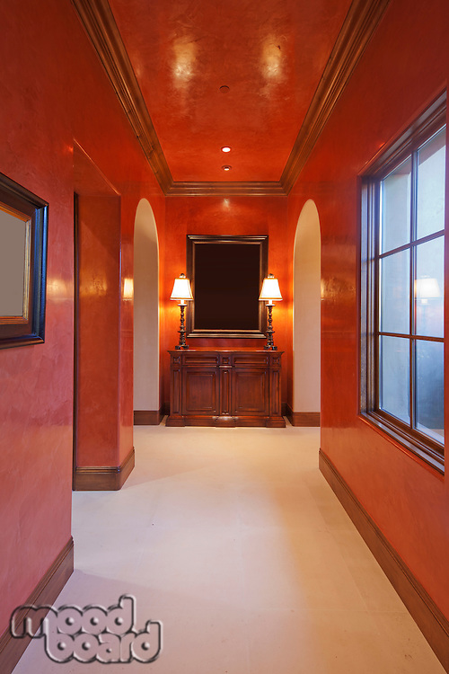 Empty red hallway with dresser and window