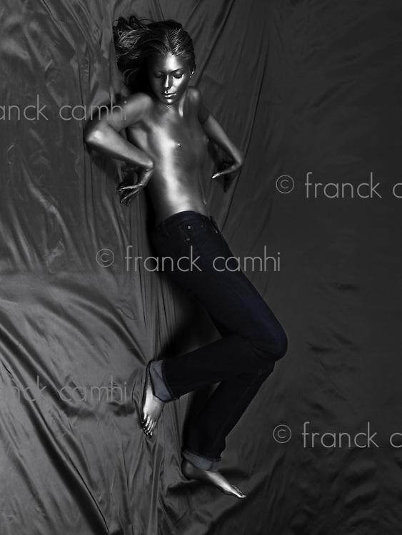 fashion pictures of a torso naked silver painted woman wearing jeans walking on walls braving gravity law