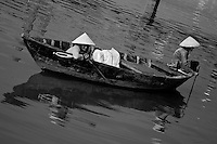Two women wearing conical hats in a small boat on the Thu Bon river in Hoi An, Vietnam.