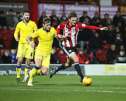 Leeds United defender and captain Liam Cooper fouling Brentford midfielder John Swift during the Sky Bet Championship match between Brentford and Leeds United at Griffin Park, London, England on 26 January 2016. Photo by Matthew Redman.