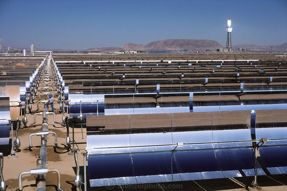 Solar energy: SEGS Solar Plant. Southern California Desert. Solar power. One of the three Luz International solar energy complexes in the Mojave Desert of California, USA. Together these sites, which cover 1000 acres, generate 275 megawatts of electricity, 90% of the world's total grid-connected solar energy production. This installation, located at Kramer Junction, has an array of 650,000 computer-controlled parabolic mirrors which track the sun across the sky, focusing it's light onto tubes containing a synthetic oil. The oil, which is thus super-heated to 391 degrees Centigrade, is used to boil water for steam turbine generators in one of five power plants. (1985).