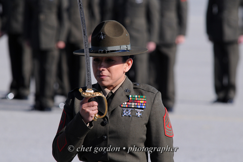 A female Marine Corps First Sergeant renders a salute with her sword during a graduation ceremony at the Marine Corps Recruit Depot (MCRD) in Parris Island, SC on Friday, March 15, 2013.