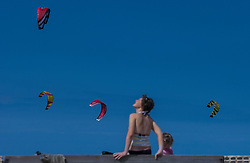 Kitesurfing kites fill the sky over the waters of the North Sea. (Photo © Jock Fistick)