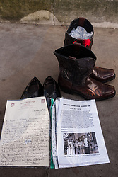 London, December 10th 2014. The shoes of hundreds of victims who died in Ireland, North and South during the Troubles are lined up opposite Downing Street as families demand that a proper investigation into over 3,600 deaths and 40,000 injuries on all sides, sets the truth free. PICTURED: A pair of shoes and cowboy boots remind us of the Miami Showband Massacre on July 31st 1975. The HET report in December 2011 concluded that collusion had taken place between British Forces and the UVF in committing this crime.