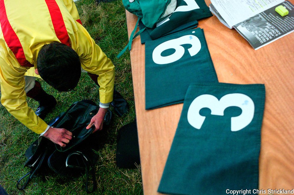 A jockey puts lead weights into his saddle to correct his weight prior to the Members race at the Jedforest Point to Point.