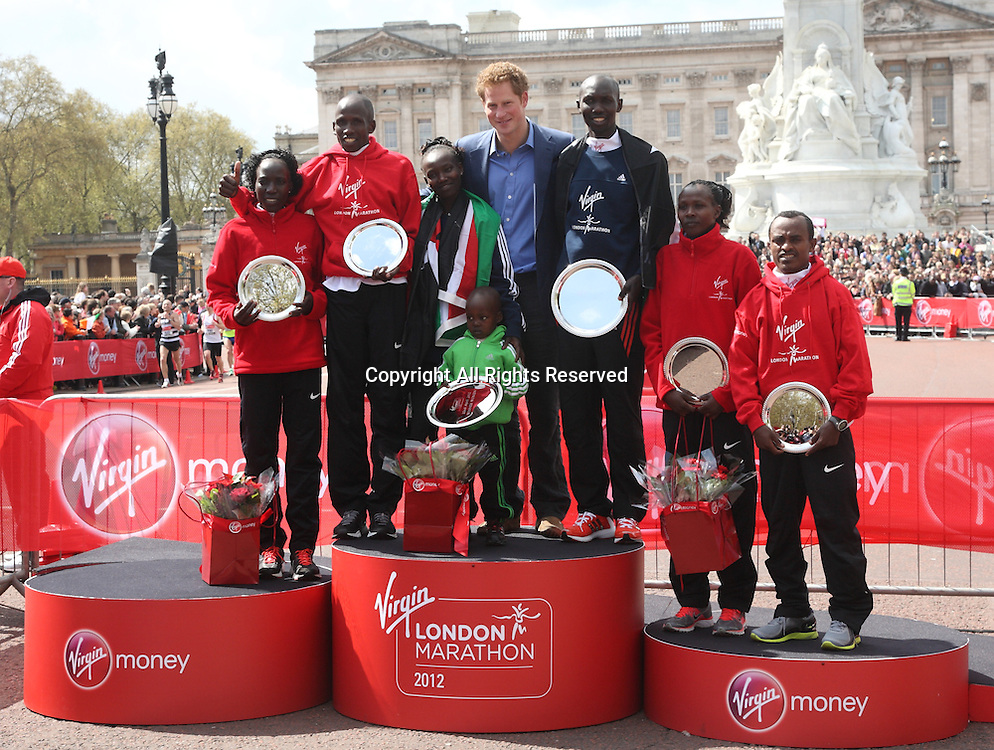 22.04.2012 London, England. The winners of the Mens and Womens races hold their trophies and pose with Prince Harry in front of Buckingham Palace on The Mall, London.