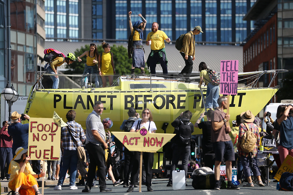 © Licensed to London News Pictures. 15/07/2019. Leeds, UK. Extinction Rebellion activists have parked a boat on Victoria bridge in Leeds city centre blocking traffic starting five days of disruption in Leeds city centre this morning. The group is targeting the financial sector in Leeds, demanding companies to 'act now to stop financing the fossil fuel industry. Other cities, including London, will be targeted by Extinction Rebellion throughout this week. Photo credit: Andrew McCaren/LNP