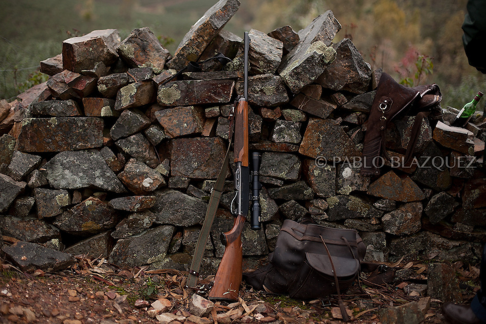 A rifle rests on a stone wall during a hunting session near Carbajo on January 19 2013, in Caceres Province, Extremadura, Spain. .Caceres has a well preserved natural environment. Plenty of its surface is dedicated to deers and wild boars hunting, making this, an important part of its economy. But most of the land belongs to large landowners. .In Carbajo, people gather three times a year to hunt deers and wild boars. In the past, they used to hunt for eating, but now days, they practice it as an sport and a social event. Then, they sell what the catch as wild game meat.