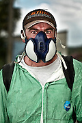 portrait of man working outdoors spraying herbal poison in fully protective clothing and mask
