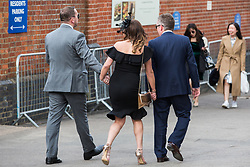 Ascot, UK. 20 June, 2019. A racegoer in high heels seeks assistance from her companions as they leave Royal Ascot after attending Ladies Day.