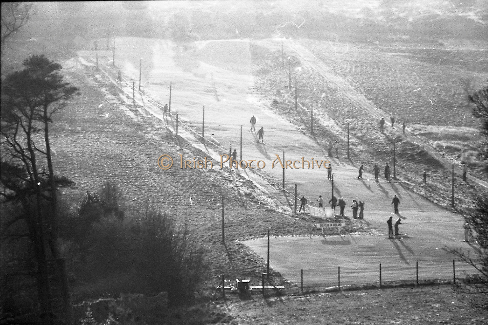 Ski-ing practice at Kilternan Sports Club. (K1).1976.25.01.1976.01.25.1976.25th January 1976..Skiers practiced on the artificial ski slope at Kilternan Sports Club in South Dublin. The ski slope is Irelands only artificial ski slope..The skiers were practicing for their holidays in colder climates. The Ski Club of Ireland was founded in 1963 and a few years later ran its first slope in Knockrabo in Mount Anville, Goatstown, south Co. Dublin..In the mid 1970's the Club moved from the suburbs to its current location in Kilternan..Pictured from a distance skiers practicing on artificial ski slope at Kilternan.