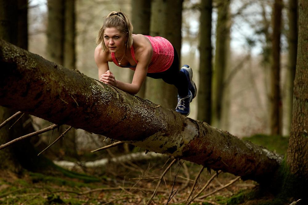 Model released - Kvinde sidder på træstamme og holder pause efter træning i skoven Kvinde træner udendørs. stykretræning i skoven som et alternativ til træningscenter - Her er det skovene omkring Århus