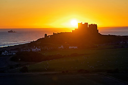 © Licensed to London News Pictures. 07/10/2012. Bamburgh, UK. Sunrise over the North Sea behind medieval Bamburgh Castle in Northumberland, UK on October 7, 2012. Photo credit : Ben Cawthra/LNP