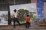 A Vietnamese artist wearing a cowboy hat paints a bucolic scene on a large canvas along the sidewalk while a little boy looks on, Vietnam, Southeast Asia