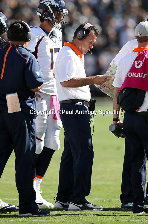 Denver Broncos head coach Gary Kubiak checks his play chart on the sideline during the 2015 NFL week 5 regular season football game against the Oakland Raiders on Sunday, Oct. 11, 2015 in Oakland, Calif. The Broncos won the game 16-10. (©Paul Anthony Spinelli)