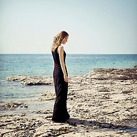 Portrait of young woman on the beach wearing a long black dress looking down to the side