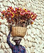 Man with basket of flowers on head, Haiti